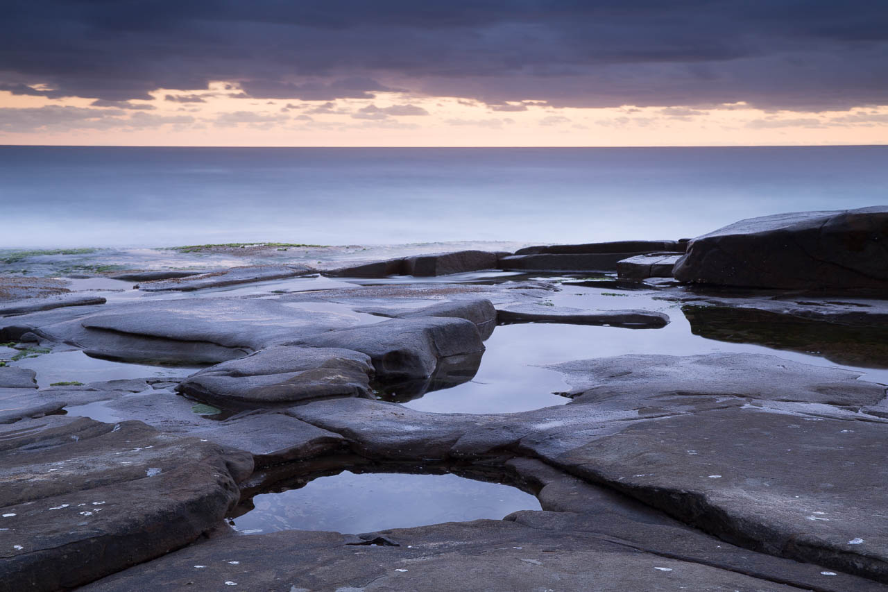 50mm: I've had to back up further and raise the tripod to try to retain the shape of the foreground pool which is becoming flattened due to perspective. The sea is bigger, the clouds are reducing and the black rock is becoming narrower and taller.