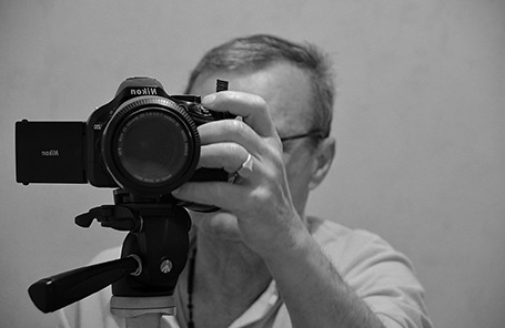 A black and white image which has a camera on a tripod while a male professional photographer is looking at the back of the camera touching with his left hand.