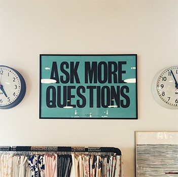 "Professional photography of a picture posted in the center of the wall between two circle clocks written ""ASK MORE QUESTION"" in semi dark green background"