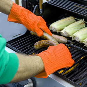 A product photography captured by Virtuous Graphics of two hands wearing an orange glove while holding some sausage over a bbq grill.
