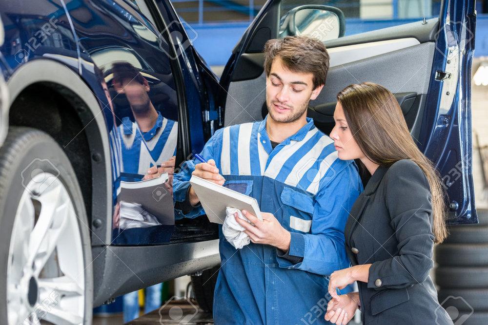 47728184-Car-mechanic-with-female-customer-going-through-maintenance-checklist-in-garage-Stock-Photo.jpg