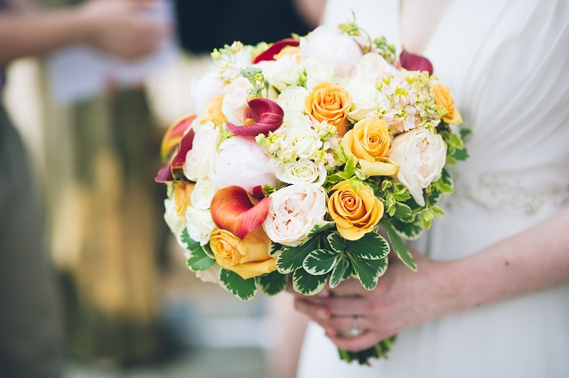 bride-holding-yellow-and-orange-flowers.jpg