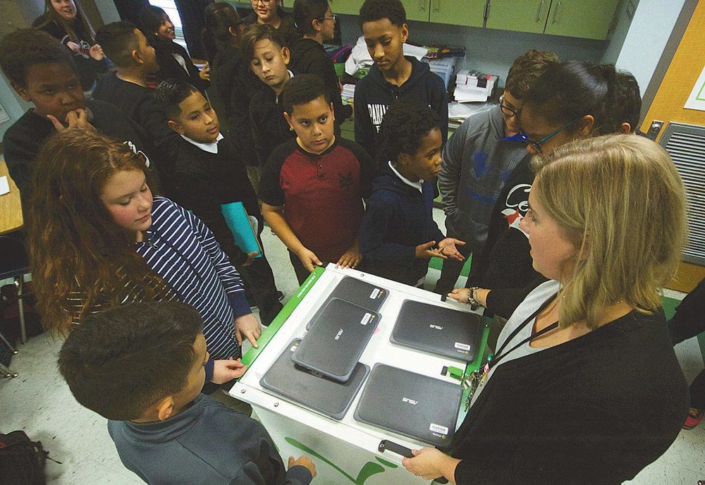 Center Street Elementary School math teacher Jenna Patout shows her students the new Chromebook computers donated Thursday afternoon to the class from the BlueFin Group.