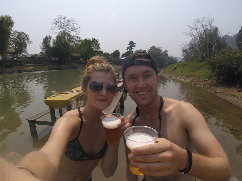 Enjoying at Beer Lao at a picnic table in the river, Vang Vieng