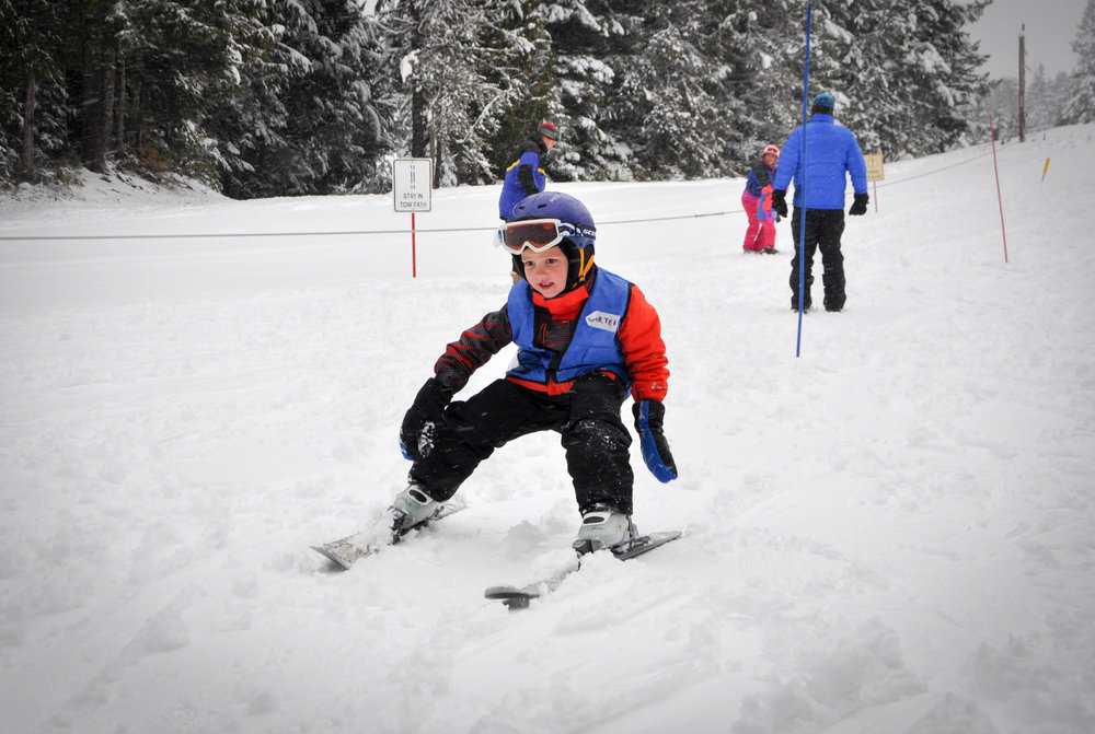 Level 2 - At the level 2 class, we apply the skills learned from level 1 to really solidify stopping on a slight slope, gliding across flats, and beginning to turn. We also ensure students can move about on skis or a snowboard up and down slight hills, so waiting in a line on skis does not become a pile of giggling kids.