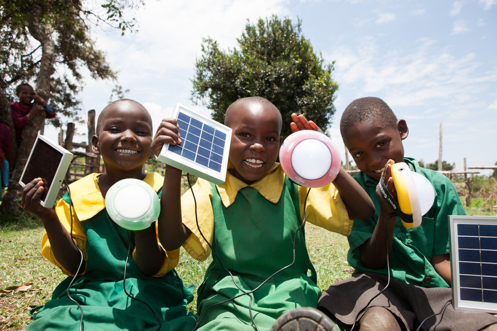 School children holding solar lanterns in Kenya, 2014.  Source: Corrie Wingate, SolarAid