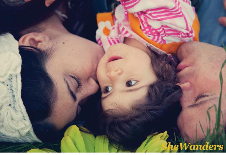 Sharon, Olivia and Sharon's husband, kissing olivia, lying on grass, San Diego Wedding Photography, She Wanders Wedding Photography