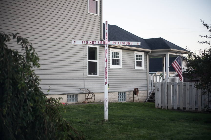 "A cross painted with ""It's not about religion! It's about relationships"" stands in a yard along West 6th Street in East Liverpool, Ohio on Sept. 15, 2016."
