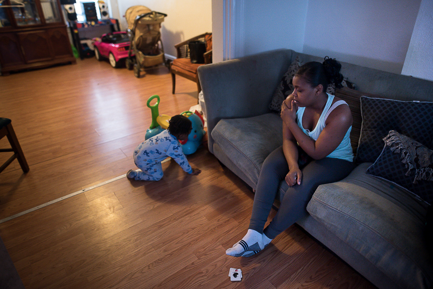 Dezmaire Baker sits on the couch watching her 2-year-old son, Dorian, play at her family's Braddock home. Dezmaire gave birth to Dorian when she was in eighth grade.