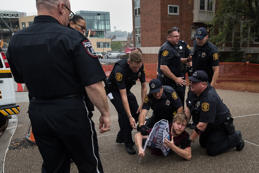A person is tackled by Pittsburgh Police after he rushed a member of the Westboro Baptist Church and ripped a sign out of their hands as they demonstrated near Carnegie Mellon University on Thursday in Pittsburgh.