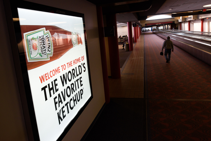 A traveler walks near a Heinz ketchup sign at the Pittsburgh International Airport on Thursday, December 14, 2017 in Moon, Pa. 