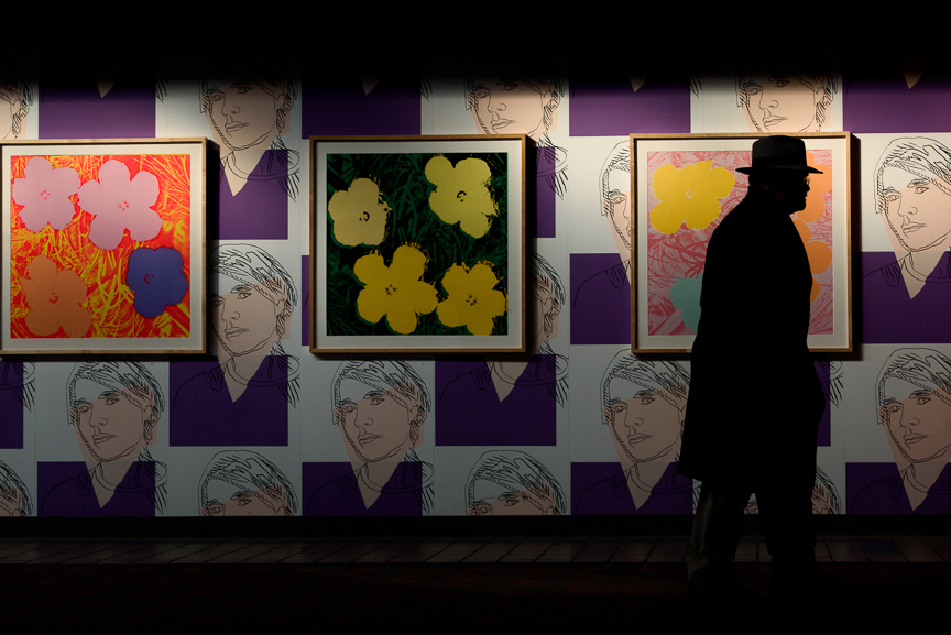 "A traveler walks near Pittsburgh native Andy Warhol's ""Self Portrait Wallpaper"" and ""Flowers"" on display at Pittsburgh International Airport on December 14, 2017 in Moon, Pa. 