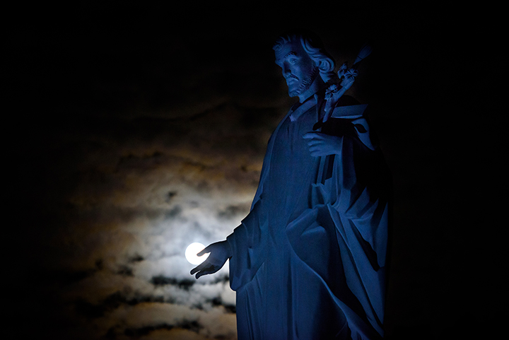 "The moon rises above a statue of Saint Joseph on Tuesday evening, January 30, 2018 at the Saint Joseph Monastery in San Bernardino County, California.  By morning the moon would put on a rare celestial show with the first ""super blue blood moon"" visible from the U.S. since 1866."