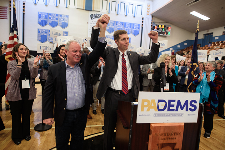 Congressman Michael Doyle, left, hoists Conor Lamb's arm after Lamb won the Democratic committee members nomination for Pennsylvania's 18th District on November 19, 2017 at Washington High School in Washington, Pa. 