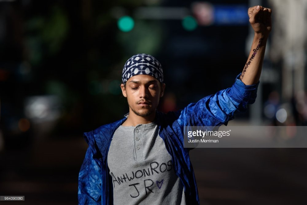 Lorenzo Rulli, 22, of McKees Rocks, Pa., pauses in a street as demonstrators hold a moment of silence as they stop traffic during a protest a day after the funeral of Antwon Rose II on June 26, 2018 in Pittsburgh, Pennsylvania. Rose was killed by an East Pittsburgh police officer on Tuesday, June 19 when he fled on foot from a traffic stop and was shot three times in the back. Days of protest and unrest have followed his death. (Photo by Justin Merriman/Getty Images)