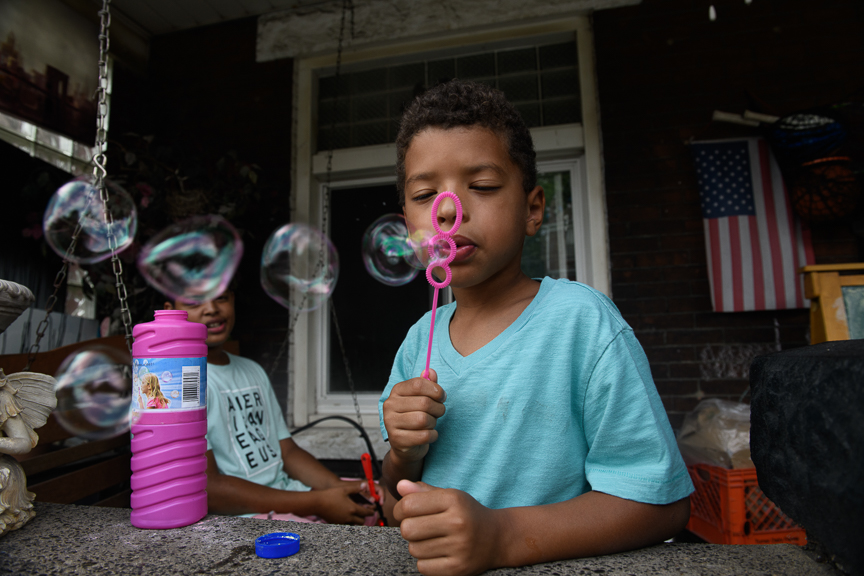 Clark Cannon, 5, blows bubbles on the front porch of his home on June 24, 2018 in East Pittsburgh, Pa.