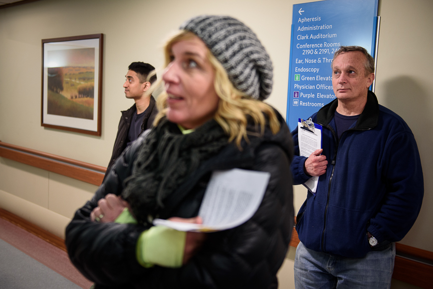 Dr. Jim Withers (right) stands with Janice Kochik, a nurse practitioner (center), and Joe Tholany, a first-year medical resident, as they wait for an elevator in a hospital prior to visiting a former patient of his on Jan. 17, 2018.