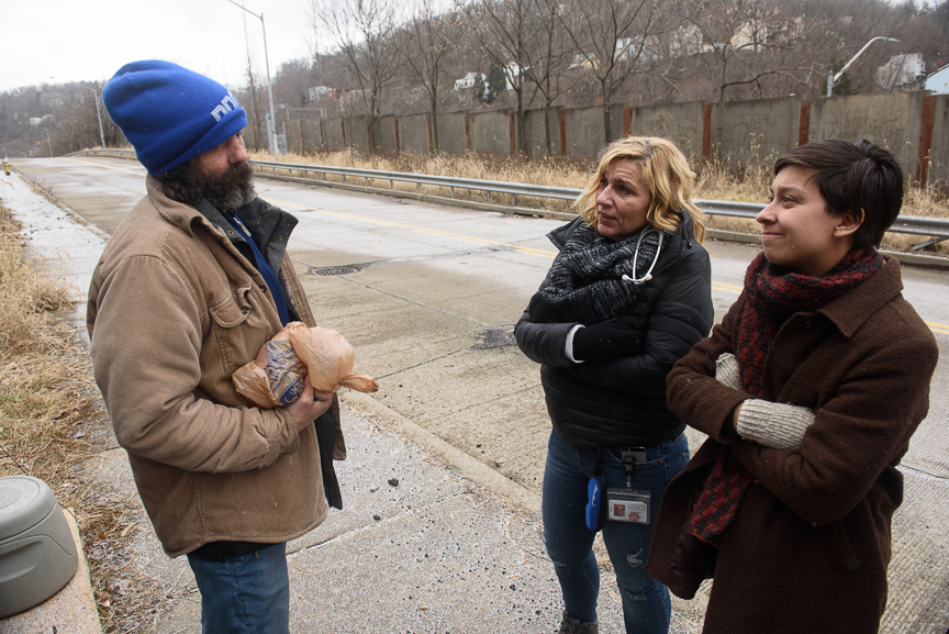 Operation Safety Net's Janice Kochik, a nurse practitioner (center), and Calla Kainaroi, an outreach specialist (right), talk with Steve Balog to check on his needs on Jan. 24, 2018, at a transitional camp for people experiencing homelessness near the North Side.
