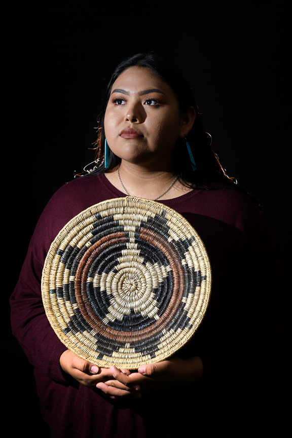 "Marion Sequaptewa, 16, holds her great grandfather's ceremonial basket, as she is photographed at San Juan High School on October 2, 2018 in Blanding, Utah. ""My Grandpa always tells me I'm not a true Navajo if I don't speak the language,"" she says. ""It's important to me because other tribes are forgetting their language. I don't want my tribe to forget ours."""