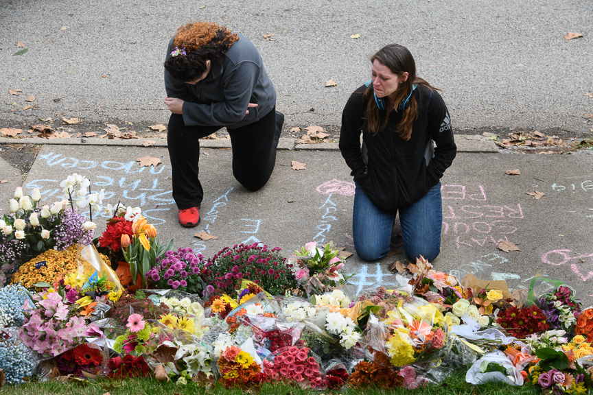 Holly Donahoo, left, and Diana Ciniello, right, both of Shadyside kneel and cry at a makeshift memorial.