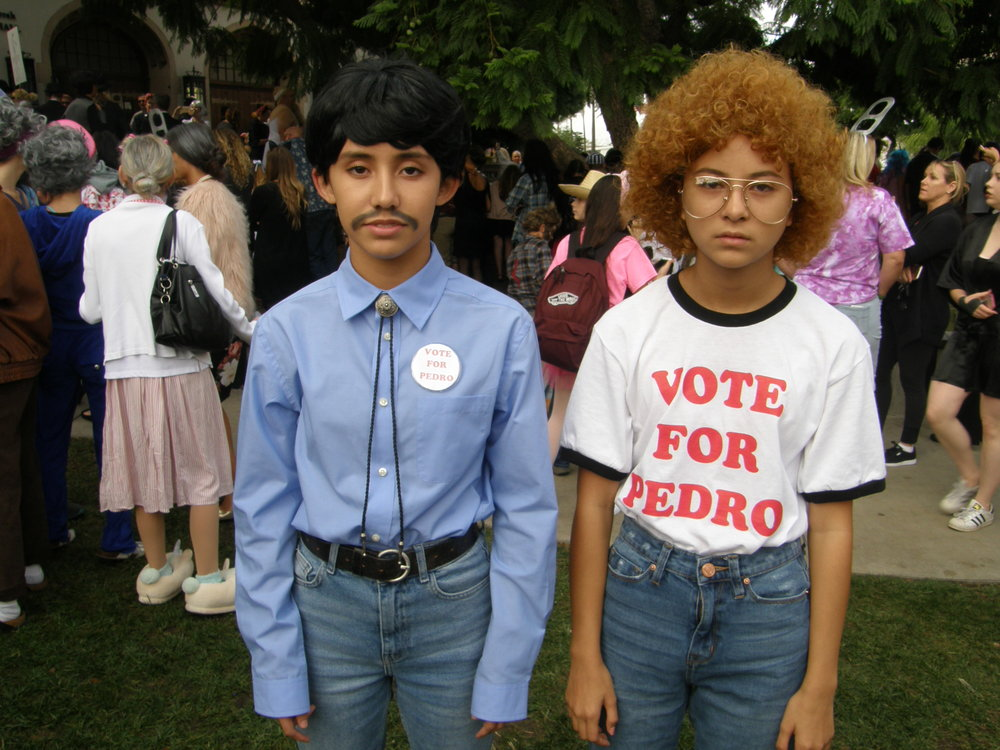 Pedro and Napoleon Dynamite, better known as sophomore Bella Machado (MT) and sophomore Isabelle Steinhorn (IA), recreate the iconic photo of the team walking down the halls as Pedro collects votes for his presidency.