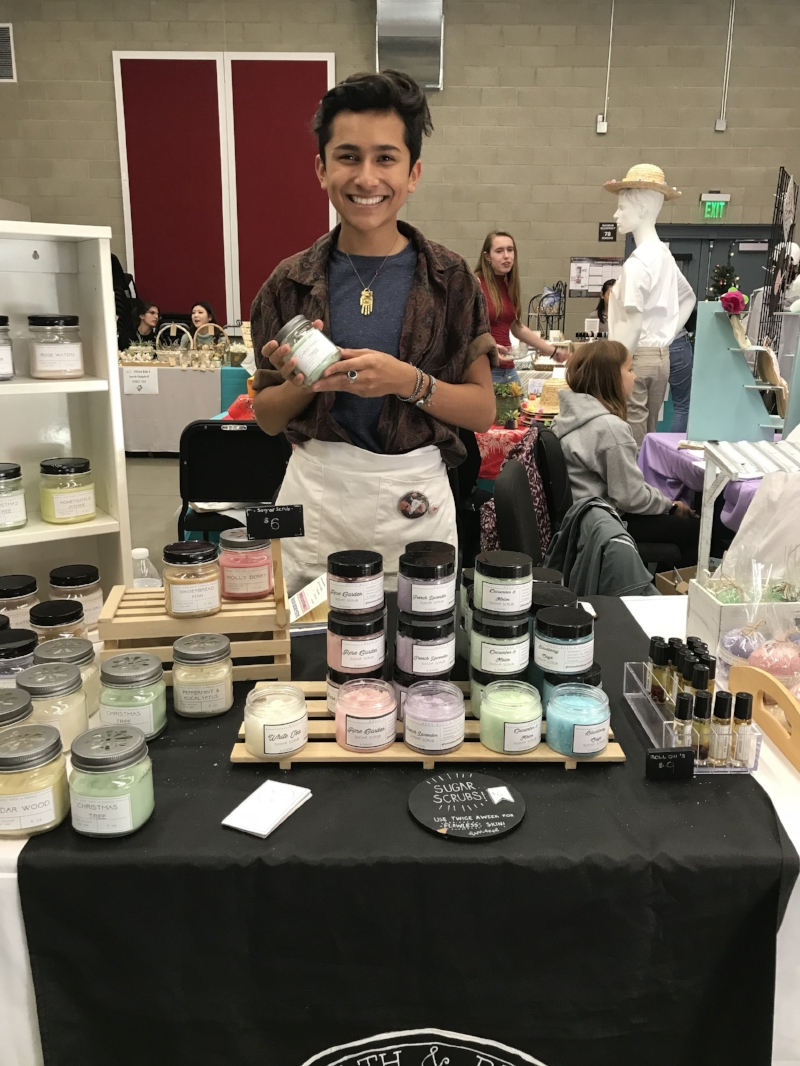 Miran Hassan (Junior VA) poses behind his booth at the Winter Market and advertises for his product line, Boho Bath and Beauty.    Photo by:   Morgan Hohenester