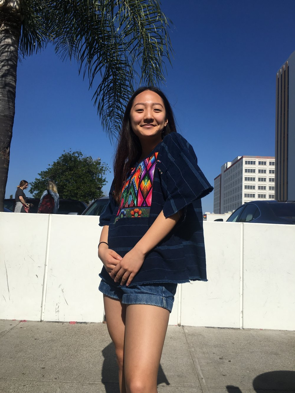 Senior Yumina Kim (VA)  Embrace the Californian flavor. Yumina wears a navy poncho with colorful, floral embroidered center she thrifted from Goodwill. She cut the sleeves off herself, and matched it with denim shorts and a pair of navy platform shoes she bought from Deelux.
