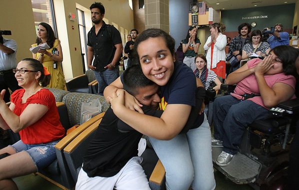 Elated students hug in response to President Obama's immigration reform announcement.