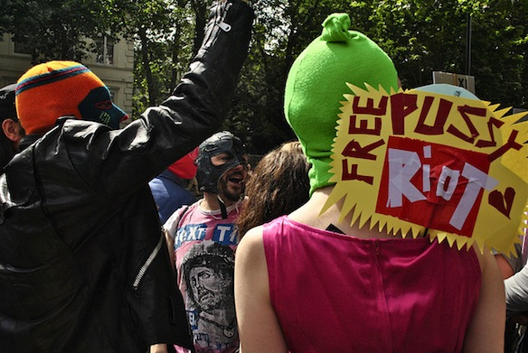 Protestors in balaclavas (as worn by members of Pussy Riot) protest Pussy Riot members' arrest.