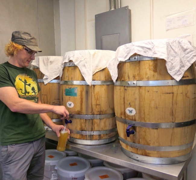 Deane Kombucha founder Bryan Bertsch pours off a sample from his oak barrel fermenters.