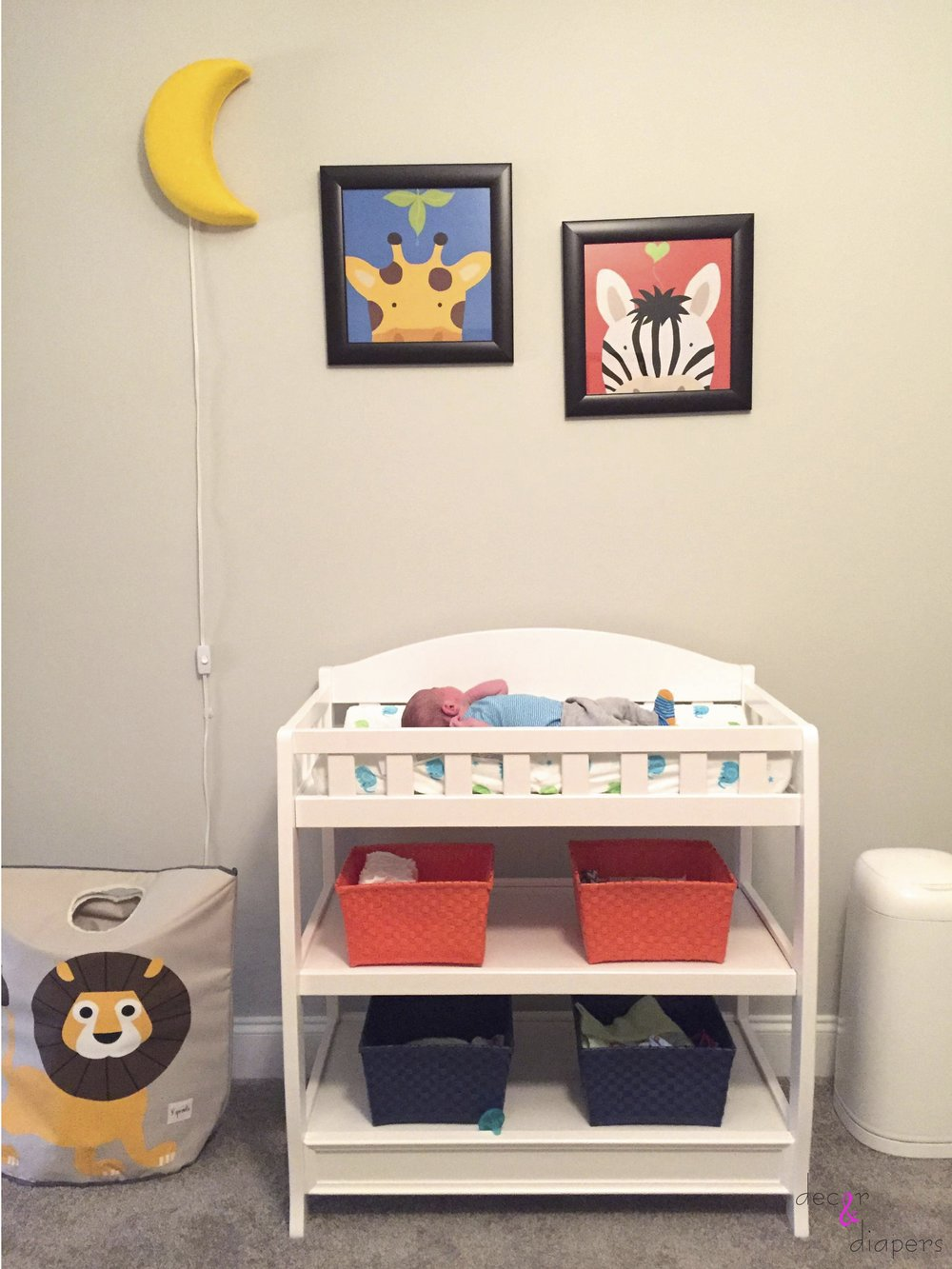 The changing table with colorful bins to hide all your baby essentials, and a glowing moon light above