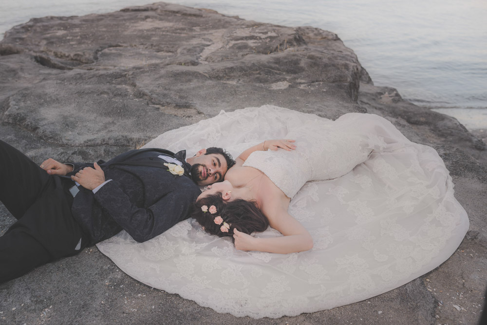 couple laying on rocks cliff {New Zealand wedding photography}