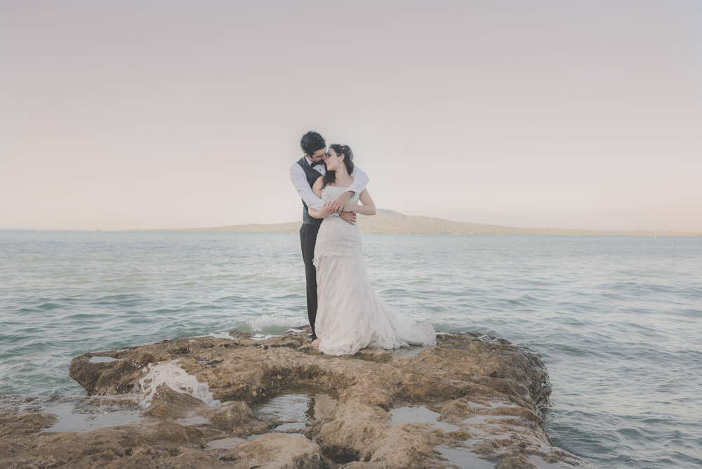 couple standing on rocks - beach weddings {Auckland wedding-engagement photographer}