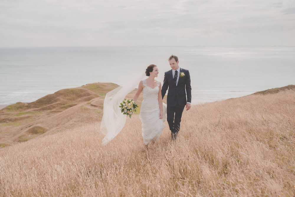 bride and groom walking on hill {Waikato wedding photographers}