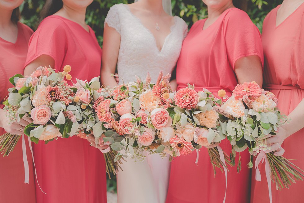 bride with bridesmaids holding flowers {New Zealand wedding photographers}