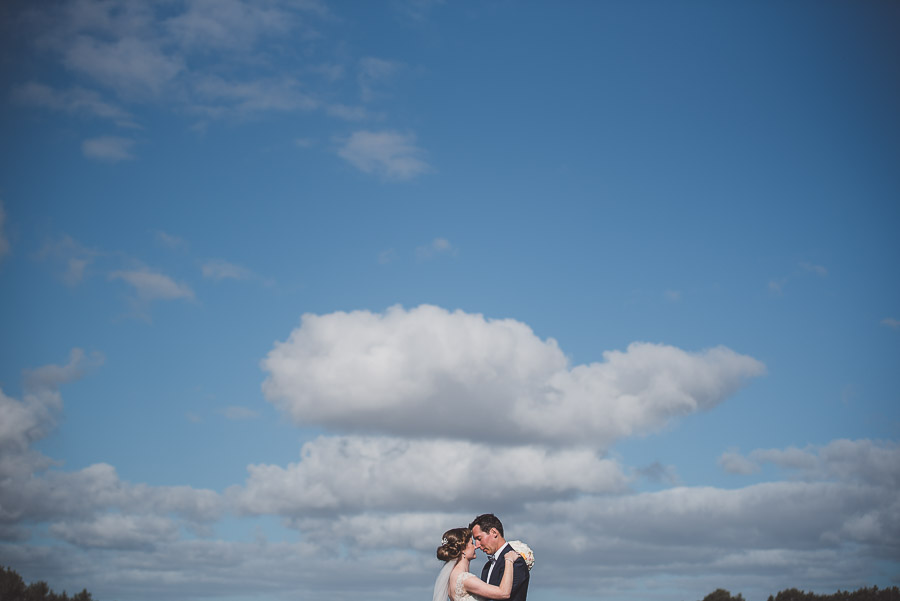 bride and groom standing with negative space of sky | Auckland wedding photographers