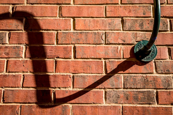 A lamp throws a shadow onto a brick wall at Eastside Village in Downtown Plano, Texas