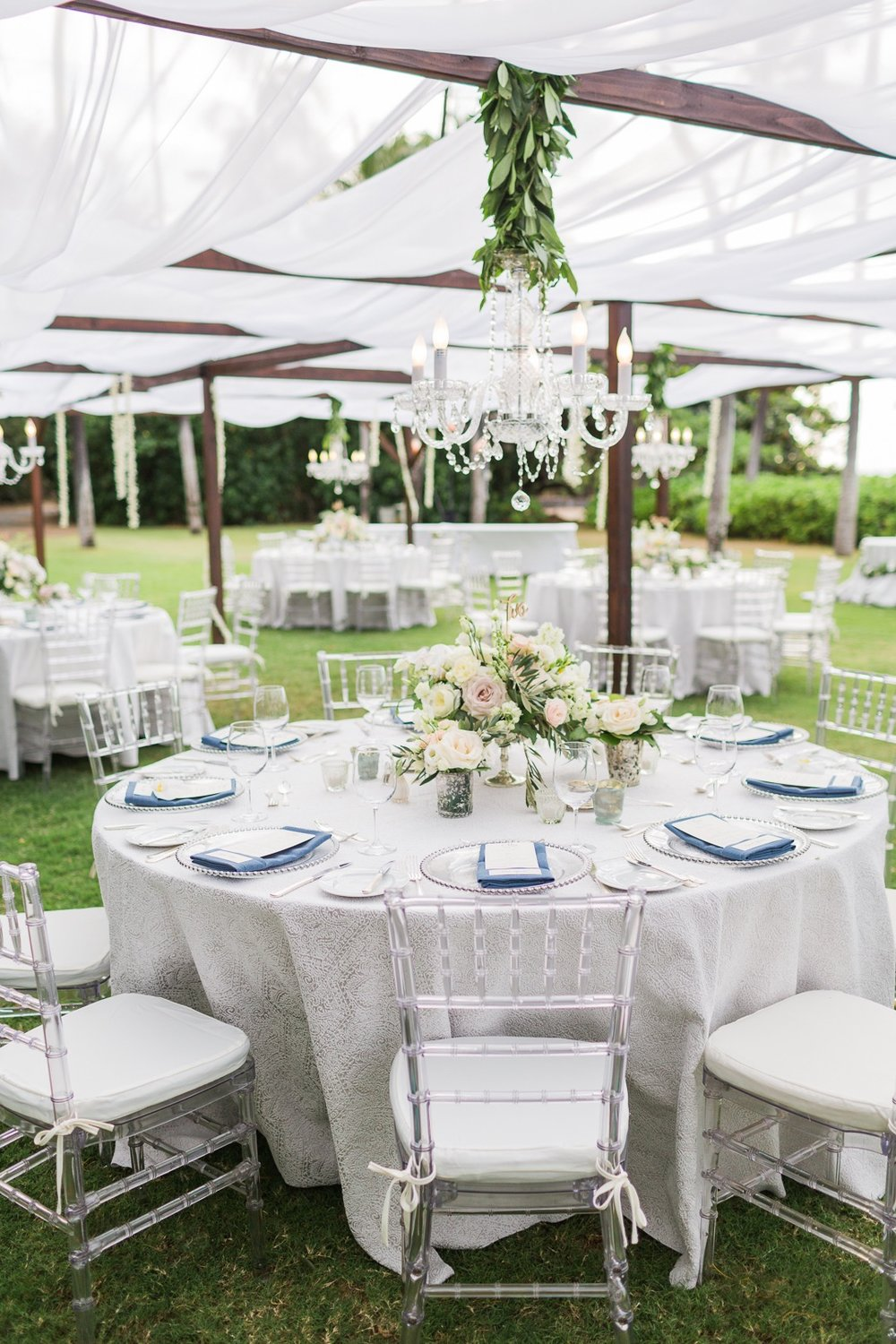 Clear Chiavari chairs with ivory cushions, silver beaded rim chargers, dark wood structure with sheer white fabric, and chandeliers.  Decor and design by Bliss In Bloom.  Photo by Fletch Photography.