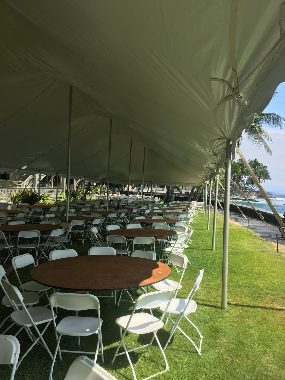 "White plastic folding chairs, 66"" round tables, and 30x wide pole tent for wedding at the beautiful seaside lawn at  Hulihee Palace ."