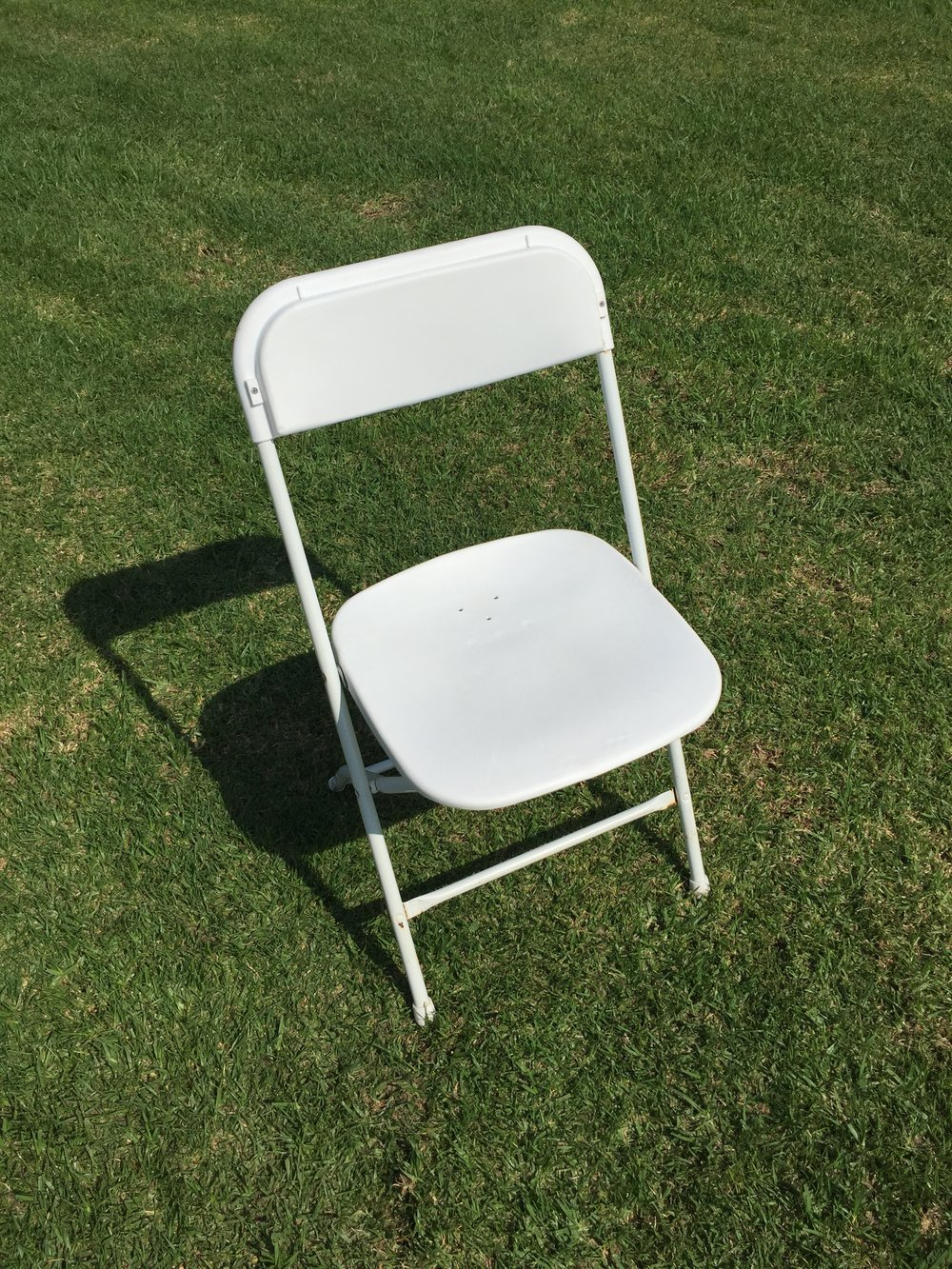 "White Plastic Folding Chair  Dimensions: 19"" wide x 17"" deep x 30"" tall"