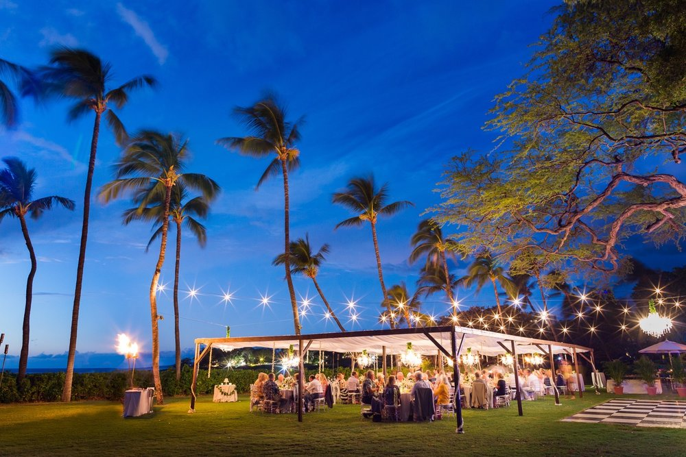 Market Lighting over our dark wood dining structure with small chandeliers and one large chandelier over the black and white dance floor for wedding at Mauna Kea Beach Hotels beautiful South point Lawn.   Event design and Coordination by Bliss In Bloom  |  Photo Sea Light Studios.