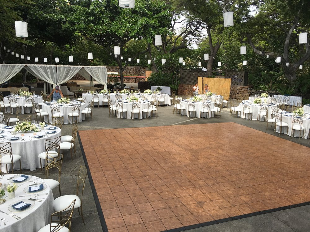 Our Teak Dance Floor set for a wedding at the Mauna Kea Beach Hotel North Point Luau grounds, along with our Gold Fan Fair Chameleon Chairs with White Cushions, Dark Wood Structure, White Lanterns and Market Lighting.  Coordinated by Bliss In Bloom.