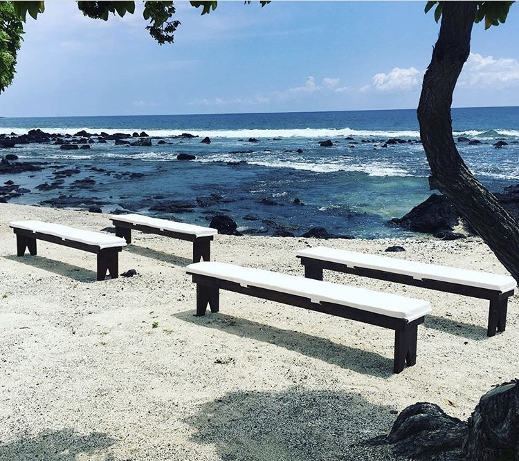 Dark Wood Benches with white cushions, set up on the beach for an intimate wedding.