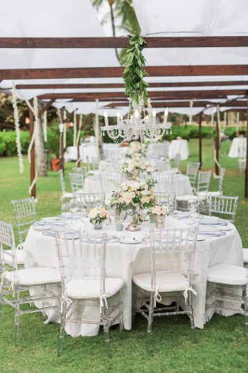 Clear Chiavari Chairs under a Dark Wood Dinning Canopy and Chandelier.  Photo Sea Light Studios
