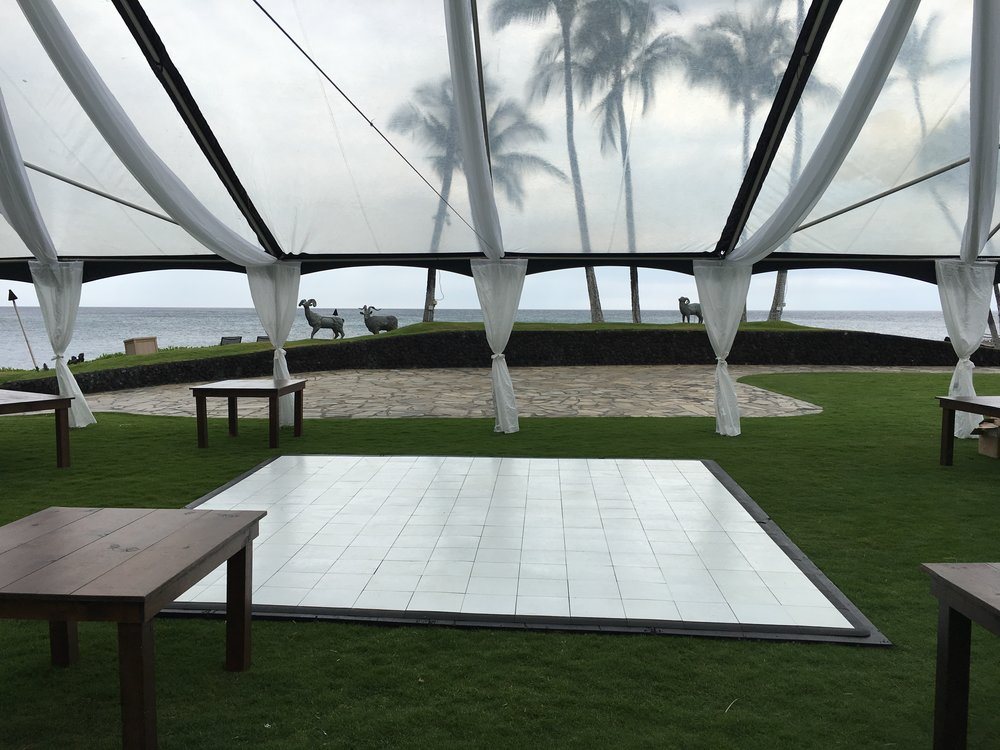 40x clear tent with black trim at the Hilton Waikoloa Ocean Terrace, with thin white leg drapes, white dance floor, farm tables, partial sheer white draping.  Coordinated by Isle Love Weddings.