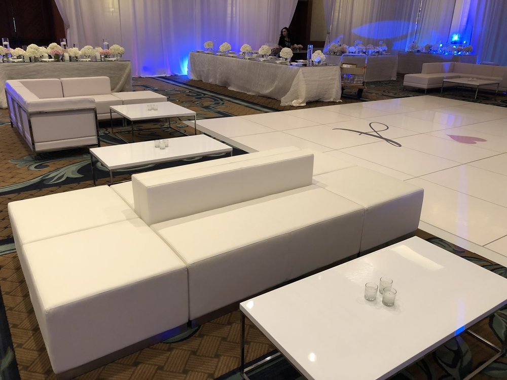 6 Piece White Leather Lounge Furniture set (in foreground) with 3 Piece White Leather Lounge Furniture (in the background) and White Coffee Table for wedding at Four Seasons Hualalai Ballroom.