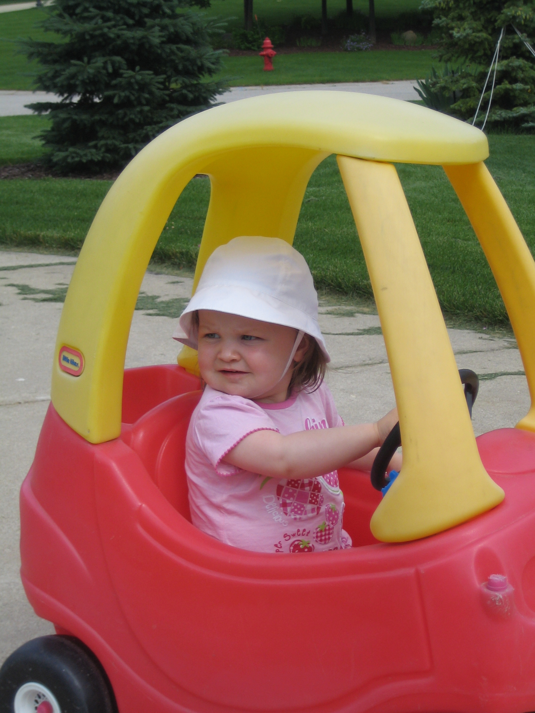 Gigi driving a toddler car.