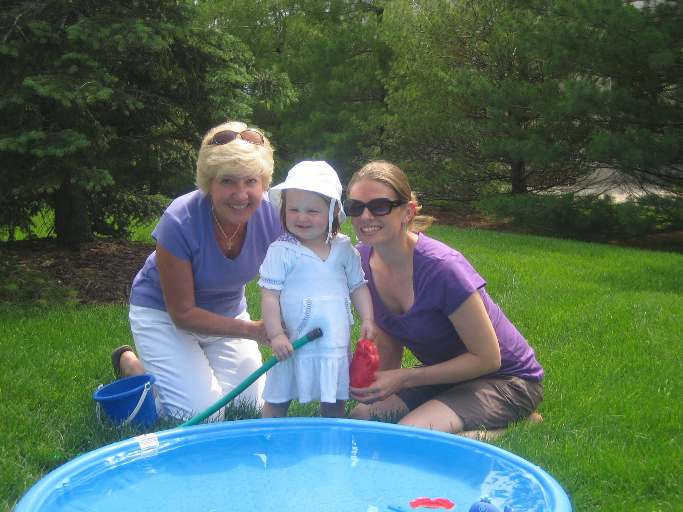 Gigi, Erika, and Linda fill the kiddie pool.