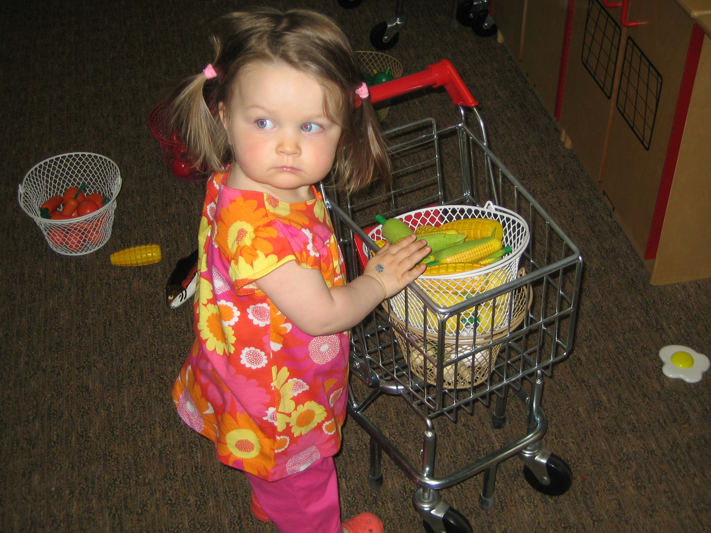 Gig pushing a child-size shopping cart.