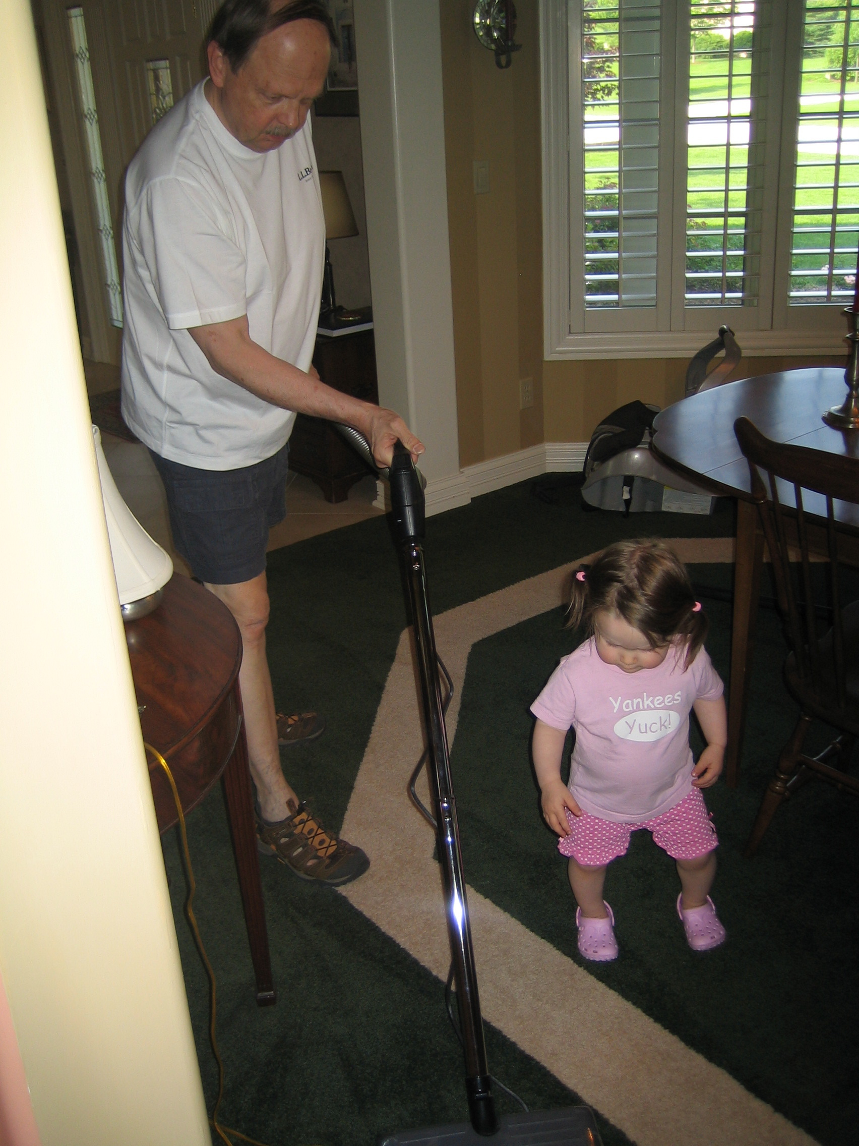 "Gigi watches her grandfather (""Farfar"") vacuum the house."